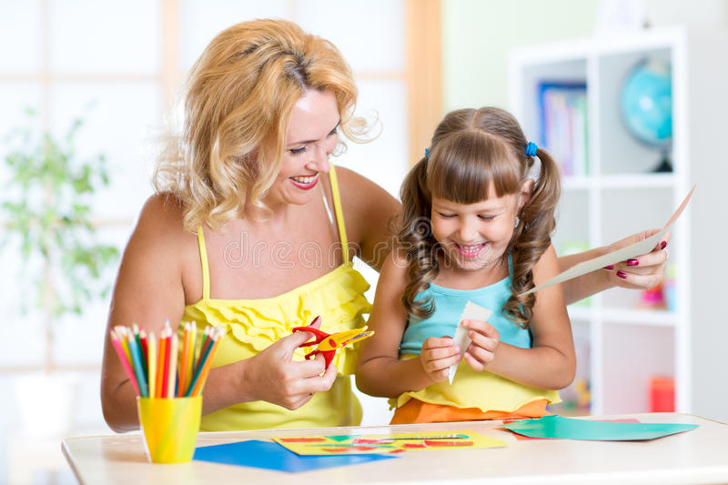 Child with woman cutting out scissors paper in stock photos