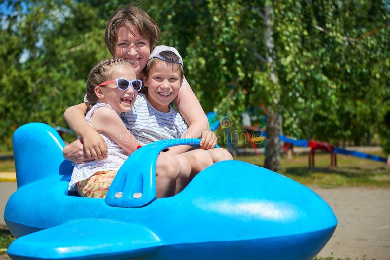 Child and woman fly on blue airplane attraction in city park, happy family, summer vacation concept royalty free stock image