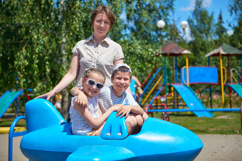Child and woman fly on blue plane attraction in city park, happy family concept, summer vacation stock photography