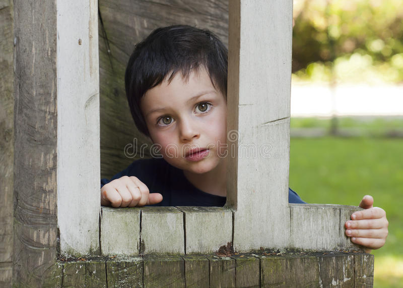 Child in wooden window royalty free stock photos