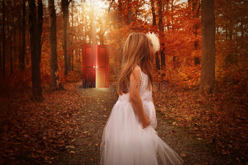 Child in Woods Looking at Glowing Red Door royalty free stock photos