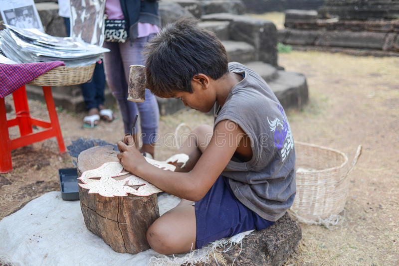 A Child worker. Making the leather carving at Angkor, Siem reap, Cambodia Date: 03 April, 2013 royalty free stock images