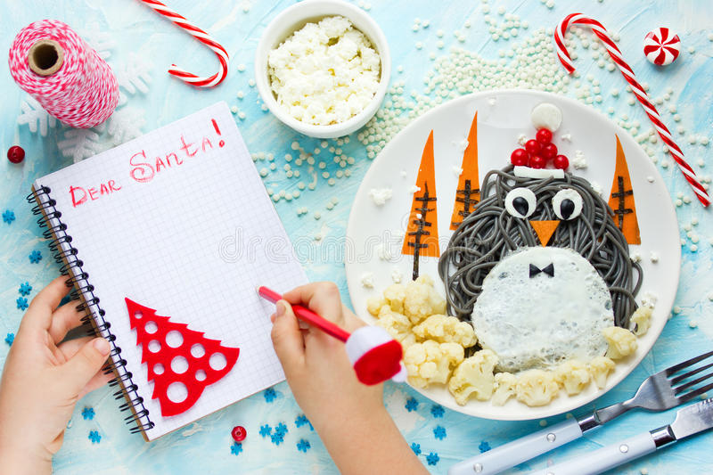 Child writes letter for santa, wish list to Christmas on table w. Ith gifts and penguin spaghetti with vegetables for funny holiday dinner stock images