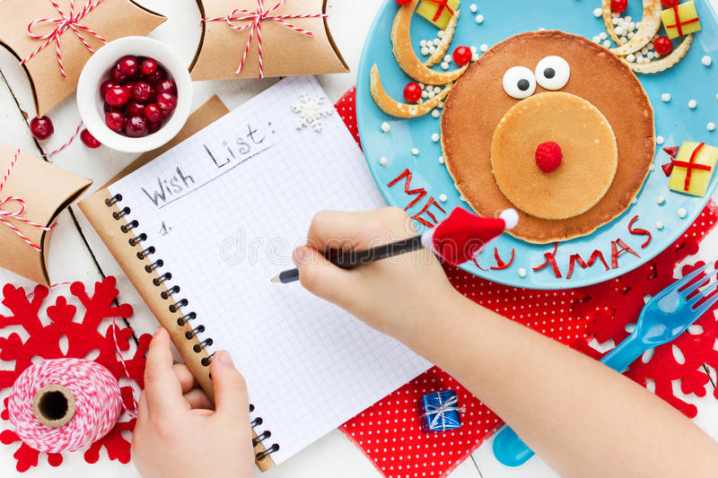 Child writes letter for santa, wish list to Christmas on table w royalty free stock photography