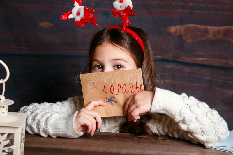 Child writes letter to Santa Claus . Funny girl in Santa hat writes letter to Santa stock image