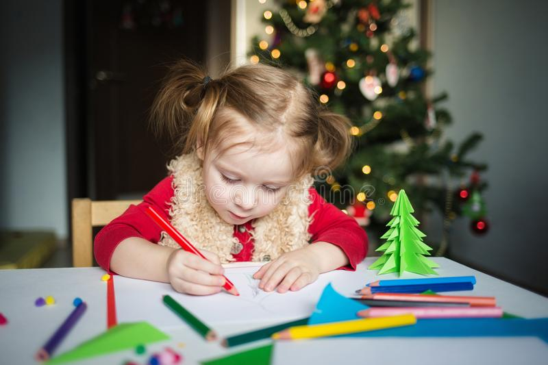 The child writes a letter to Santa Claus. a little girl draws with crayons on the background of the Christmas tree royalty free stock photo