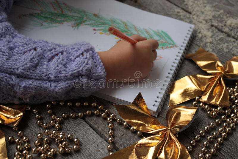 Child writes letter to Santa and draw a Christmas tree. stock photos