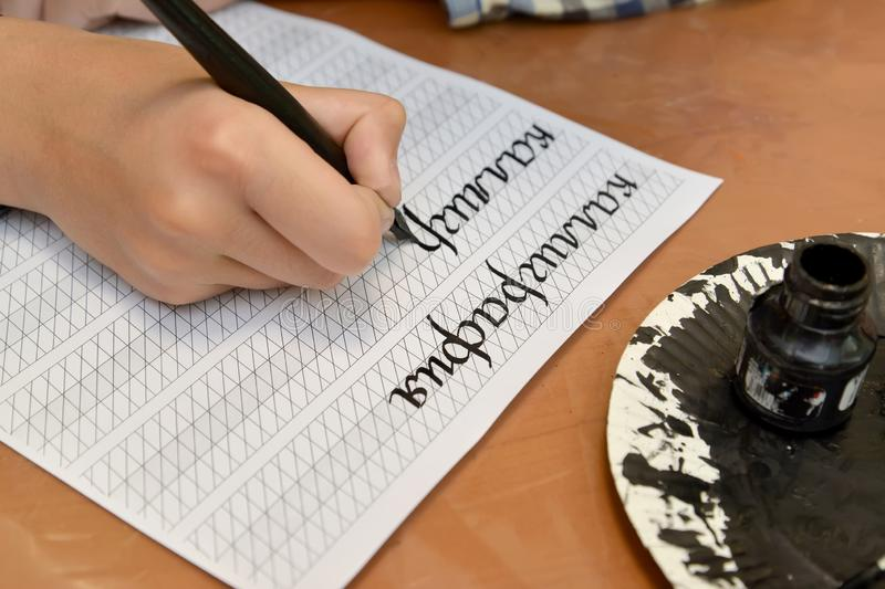 The child writes the word  `calligraphy` with a fountain pen. The Russian text - a calligraphy royalty free stock photography