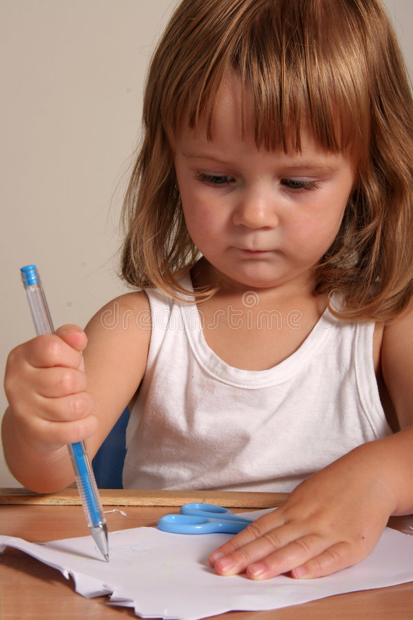 Child writing. With blue pen royalty free stock image