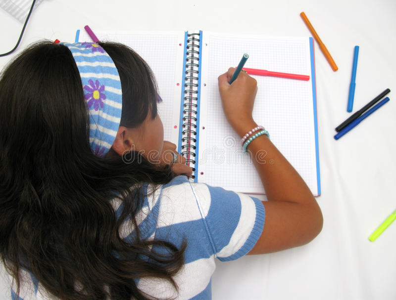 Child writing. On the book over white stock photos