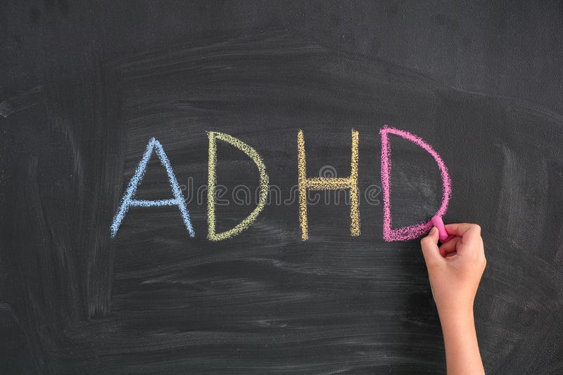 Child writing Abbreviation ADHD on a blackboard. ADHD. Child writing Abbreviation ADHD on a blackboard. ADHD is Attention deficit hyperactivity disorder stock images