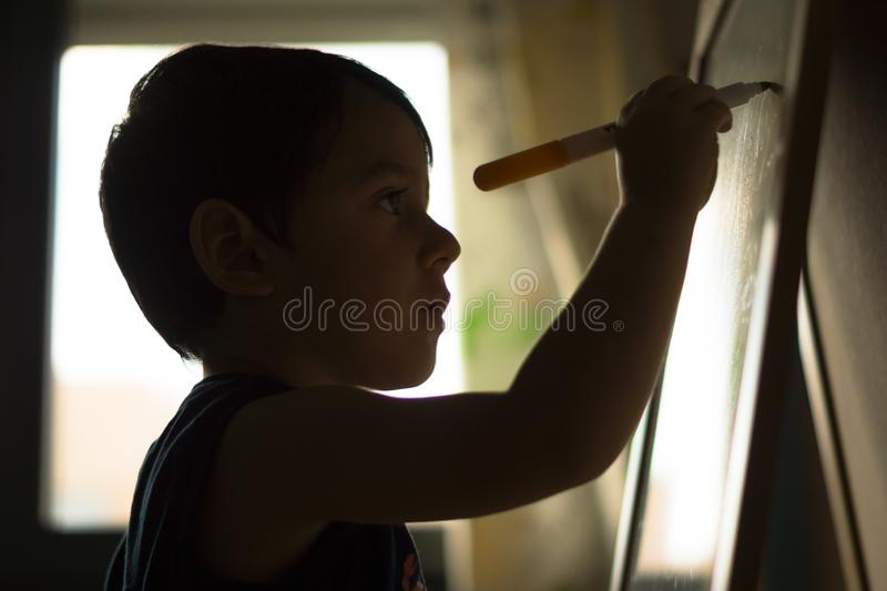 Child writing on a blackboard. With marker pen against medium plane light royalty free stock photo