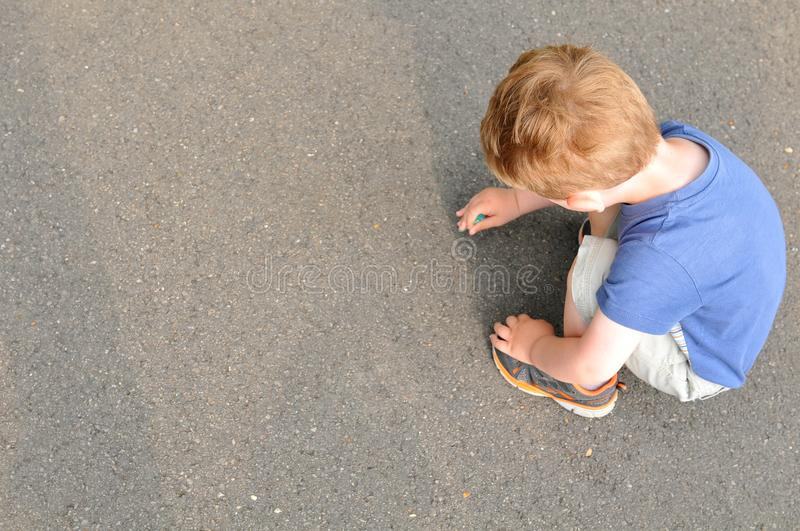 Child writing. With chalk on concrete stock images