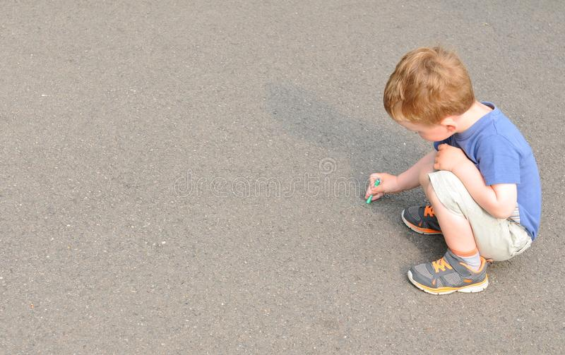 Child writing. With chalk on concrete royalty free stock image