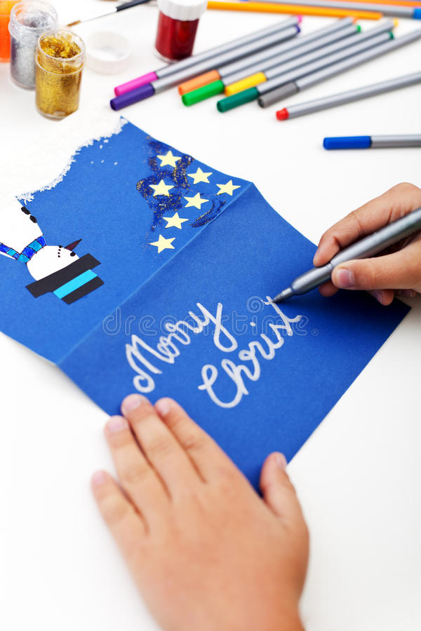 Child writing christmas greeting card. Child writing on christmas greeting card made by hand stock photography