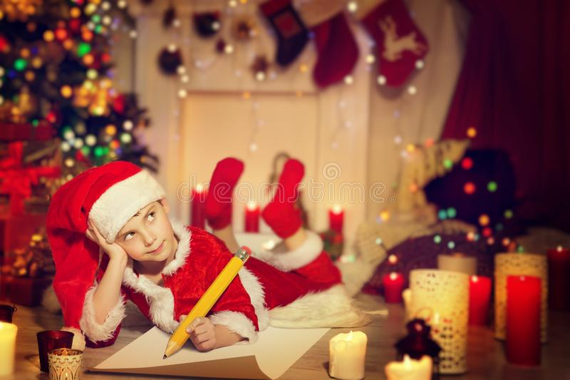 Child Writing Christmas Letter, Happy Kid Write Santa Wish List. Child Writing Christmas Letter, Happy Kid Write Wish List to Santa in Decorated Xmas Home Room royalty free stock images