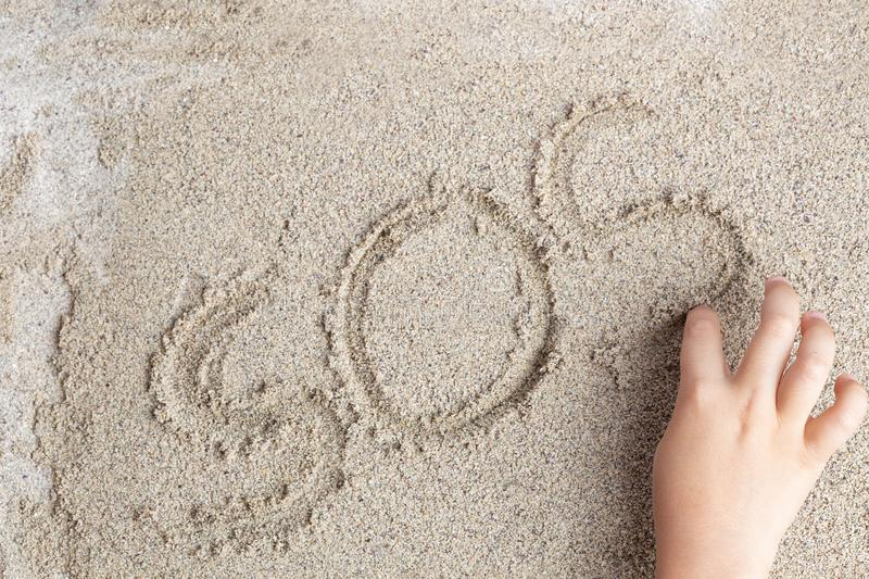 A child is writing a finger on the sand of the word SOS stock images