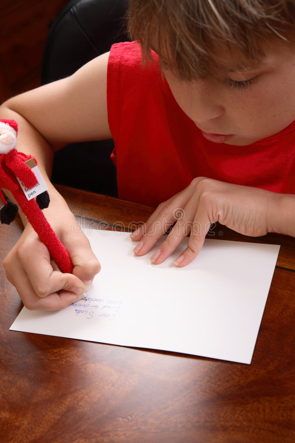 Child writing a letter. A child writing a letter to santa. Focus to hands royalty free stock images