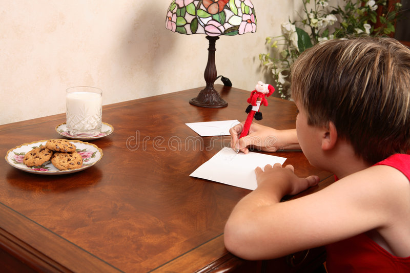 Child writing letter at table royalty free stock photos