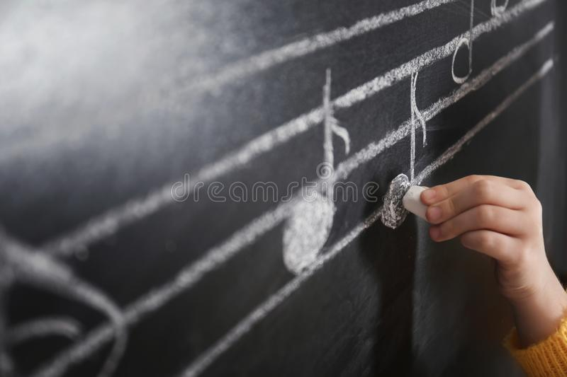 Child writing music notes on blackboard. Closeup stock images