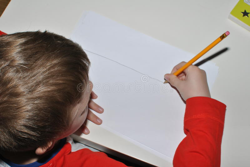 Child writing with pencil. Small hand writing with pencil royalty free stock photos