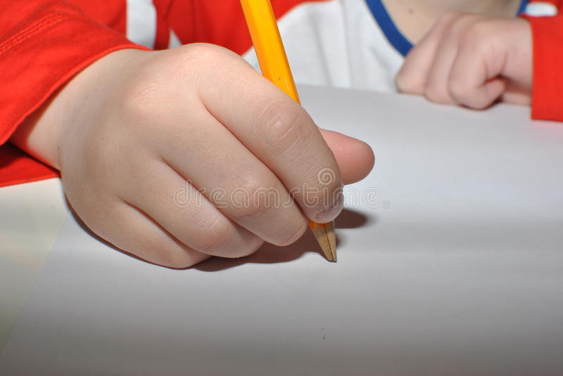 Child writing with pencil. Small hand writing with pencil stock photo