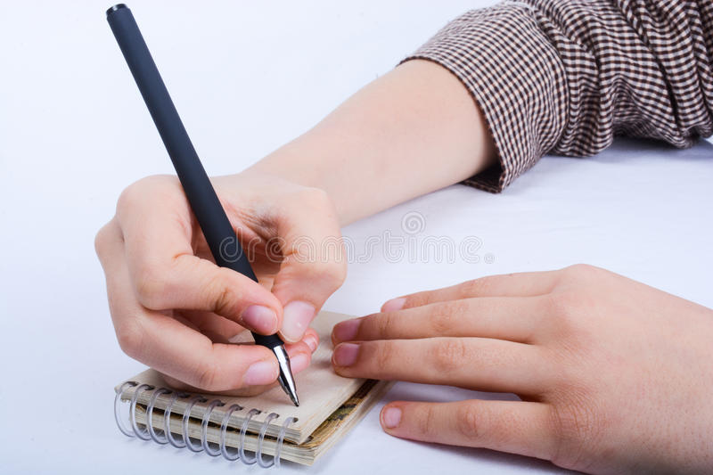 A child writing on a spiral notebook. A child hand is writing with pen on a spiral notebook on white background stock photography