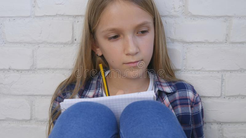 Child Writing, Studying, Thoughtful Kid, Pensive Student Learning Schoolgirl stock image