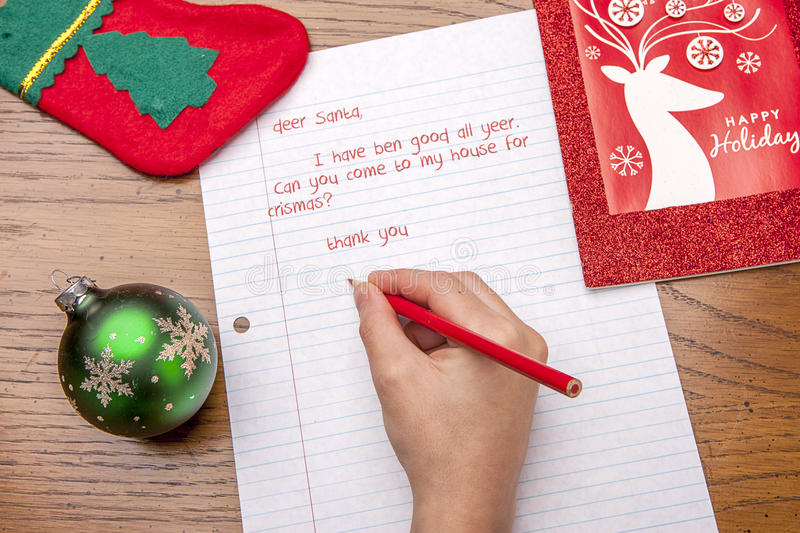 Child writing to Santa. Picture of a child`s hand writing a letter to Santa stock image