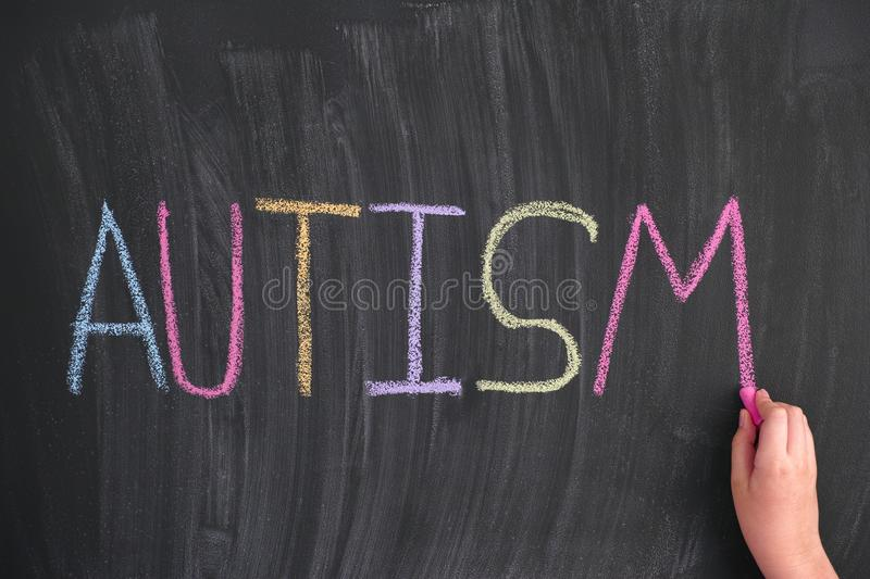 Child writing the word Autism on a blackboard. Close up royalty free stock photo