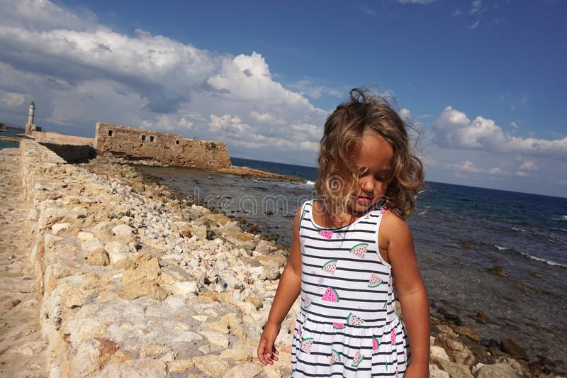 Child of 3-4 years in Chania, Crete with the background of the walls of the Venetian harbor stock photography
