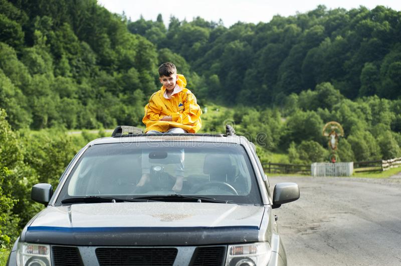 Child in Yellow Jacket Sitting on Roof of Nissan Frontier Through the Sunroof royalty free stock photos