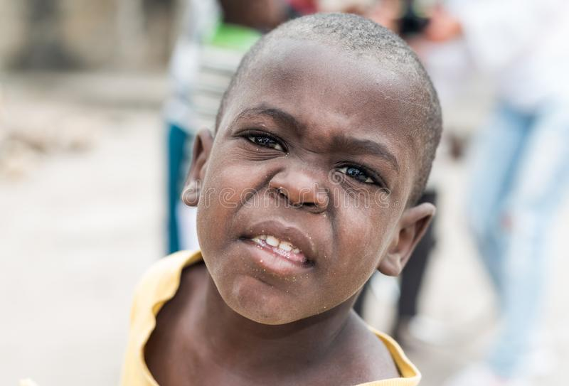 Child of zanzibar, tanzania with his head shaved. Zanzibar, Tanzania - July 15, 2016: African child of zanzibar, tanzania with his head shaved looking upward royalty free stock images