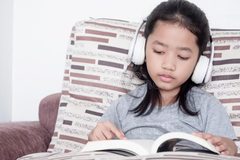 Childern reading a book on the sofa royalty free stock images