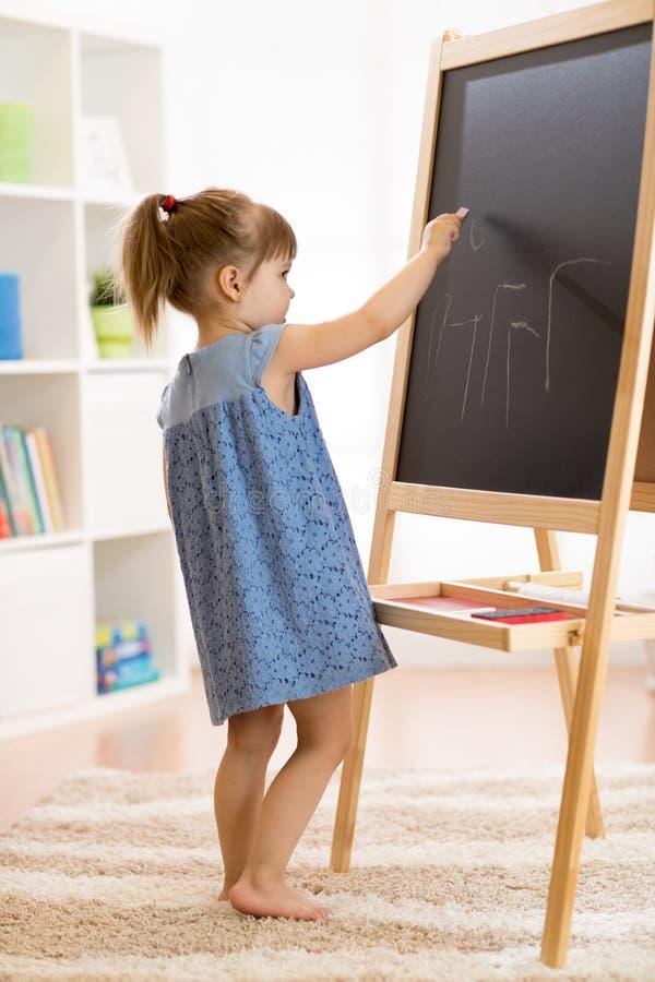 Childgirl dessine avec la craie sur le tableau noir photo stock