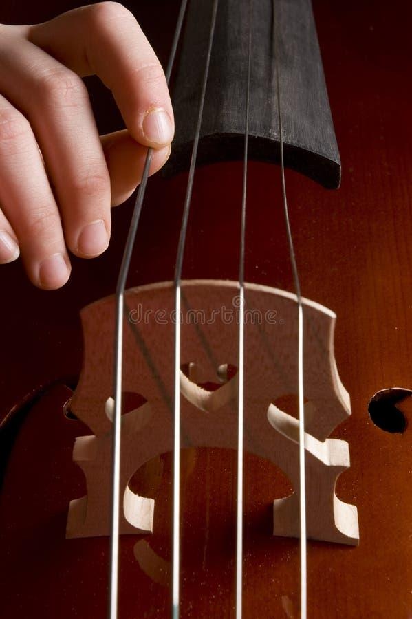 Childhand spielt das Cello stockbilder