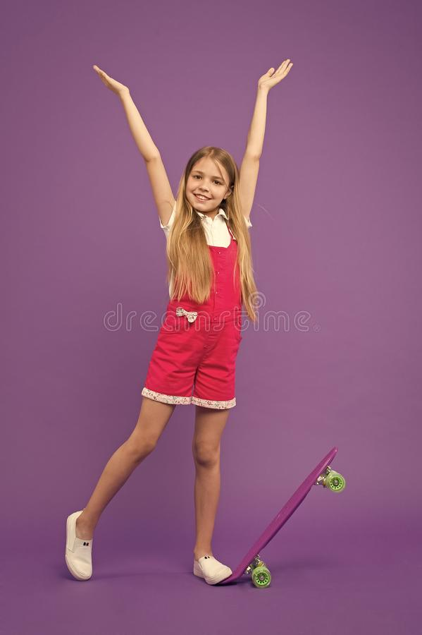 Childhood and active games. Small girl smile with skate board on violet background. Carefree day. Child skater smiling. With longboard. Skateboard kid in pink royalty free stock photo