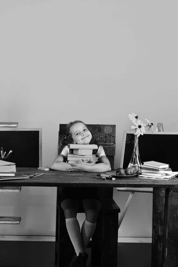 Childhood and back to school concept. Girl sits at desk with colorful stationery, flowers and fruit stock photo