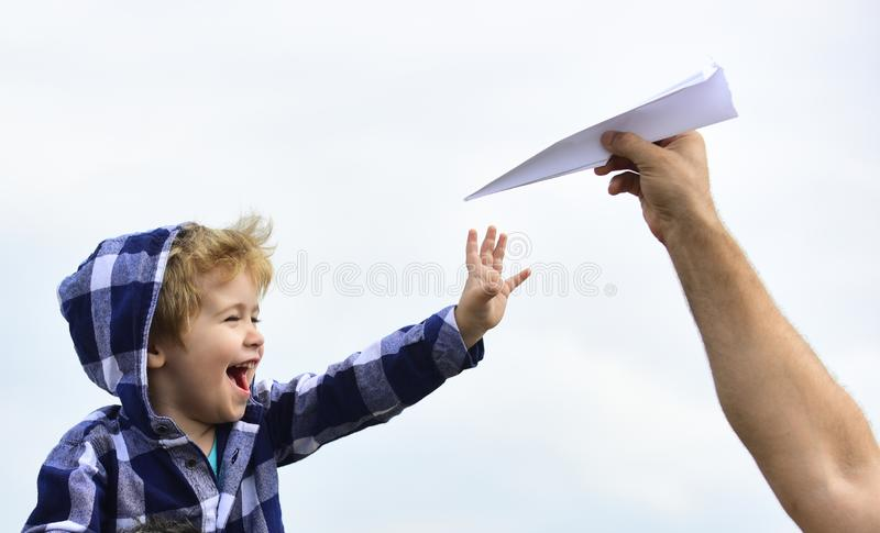 Childhood. Child son playing with paper airplane. Carefree. Freedom to Dream - Joyful Boy Playing With Paper Airplane. Dream of flying. Enjoy stock images