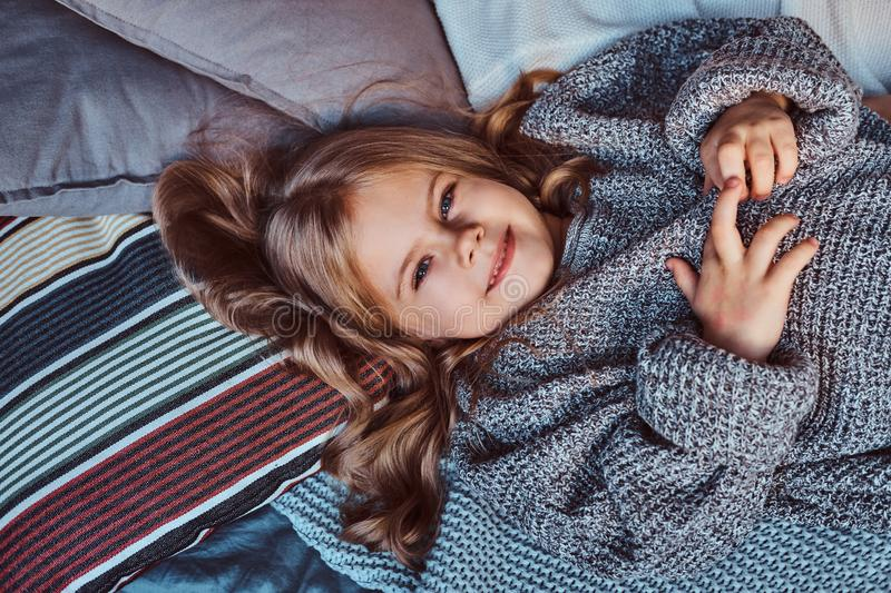 Close-up portrait of a little girl in warm sweater lying on bed. stock photography