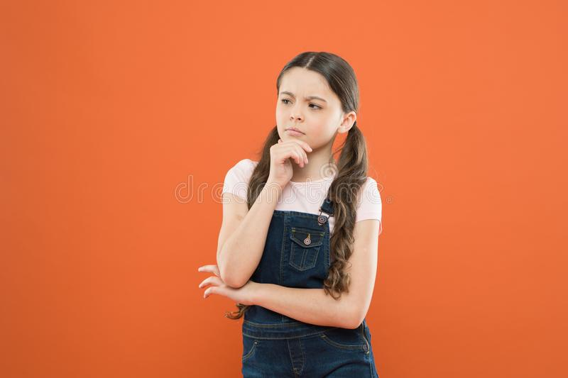 Childhood concept. Fashion girl. Girl adorable kid stand over orange background. What is key to childhood happiness royalty free stock photos
