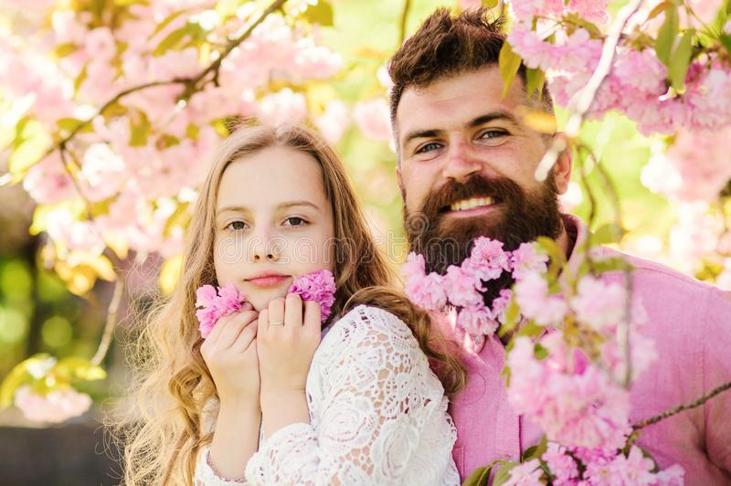 Childhood concept. Father and daughter on happy faces play with flowers, sakura background. Girl with dad near sakura stock photography