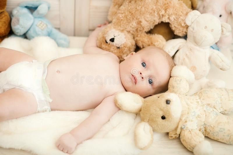 Childhood and curiosity concept. Baby boy with his soft toys. Selective focus. Baby in diaper lying on soft white blanket. Newborn toddler with blue eyes and stock images