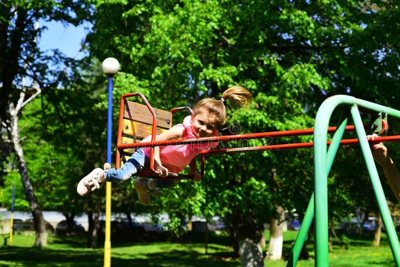 Childhood daydream .teen freedom. Small kid playing in summer. Playground in park. Happy laughing child girl on swing royalty free stock photo