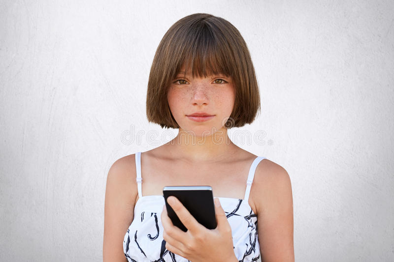 Childhood in digital age. Cute girl with short stylish hairdo, dark deep-set eyes and freckles wearing nice dress, holding smart p. Hone in her hands, playing stock image