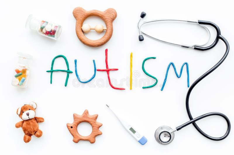 Childhood diseases. Word autism near stetoscope, pills, toys on white background top view stock photography