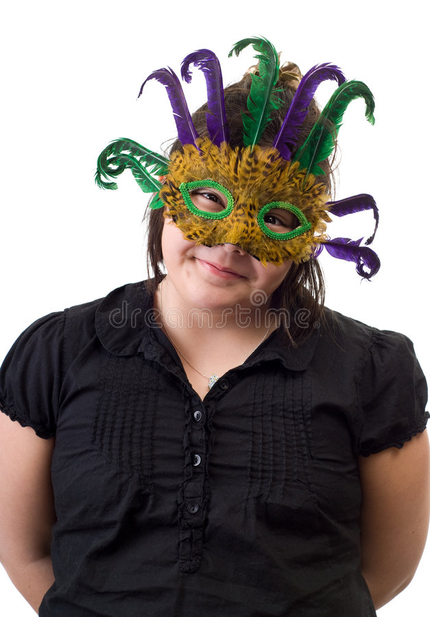 Childhood Dress-up. A young girl playing dress-up and wearing a feather mask, isolated against a white background stock photos