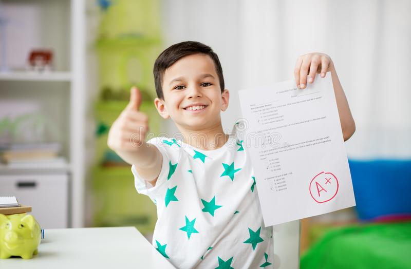 Happy smiling boy holding school test with a grade royalty free stock photos