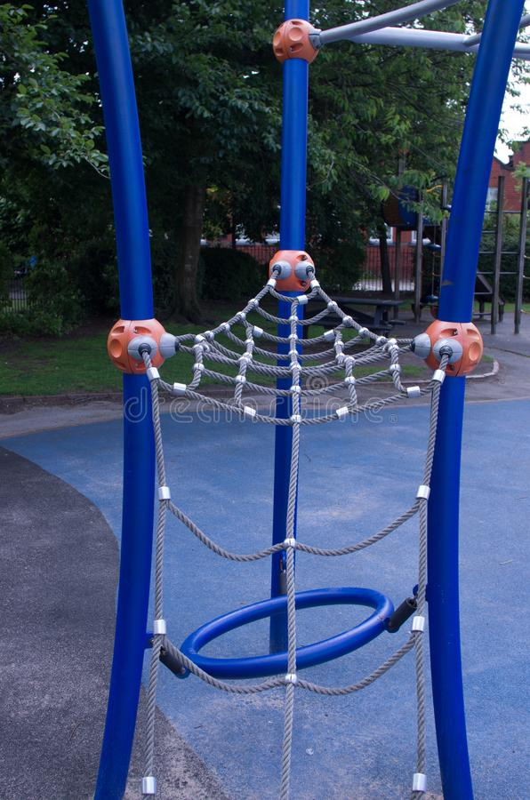 Childhood, equipment and object concept - climbing frame with slide on playground outdoors at summer royalty free stock photography