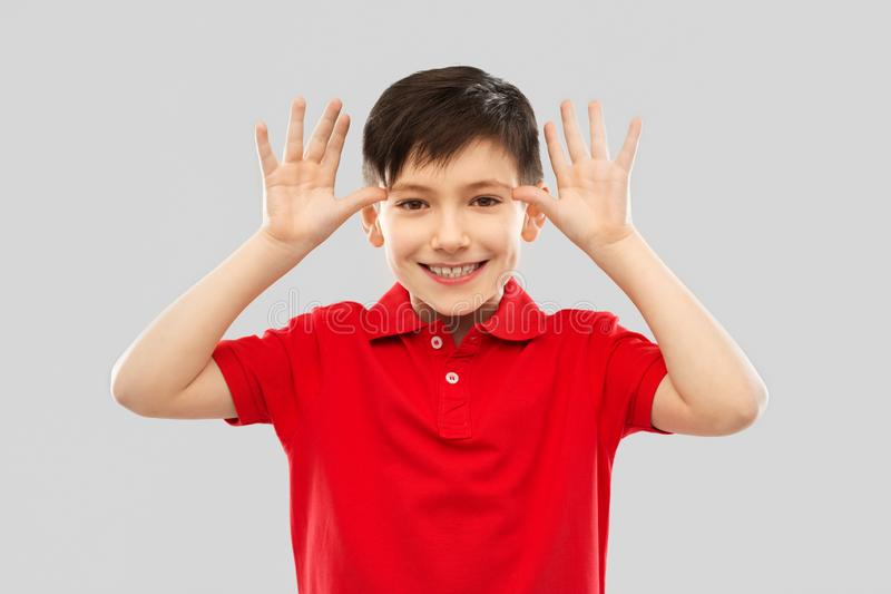 Little boy in red t-shirt making big ears by hands stock photography
